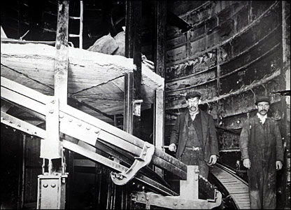 Workers at Holloway station's spiral moving staircase in 1906