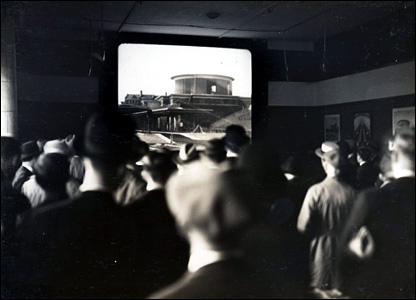 Public at Charing Cross looking at a short film about new Arnos Grove station in 1932