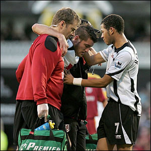 Fulham's Liam Rosenior (right) looks concerned as his team-mate Franck Queudrue is carried off with an injury