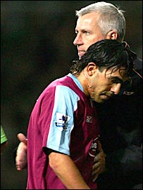 Carlos Tevez walks past West Ham boss Alan Pardew after being substituted