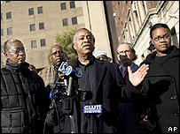 Al Sharpton, flanked by relatives of the injured men