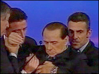 Silvio Berlusconi is helped by aides as he collapses