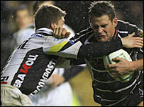 Ospreys' Lee Byrne (right) holds off a Calvisano defender