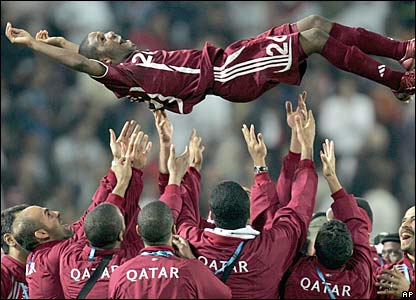 Khalfan al-Khalfan of Qatar is thrown into the air by his team-mates as they celebrate after beating Iraq 1-0 to win the gold medal in the final of the Men's soccer competition