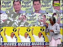 A woman stands by posters of Ecuador's two run-off candidates