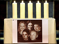 Five candles burn above a picture of the women