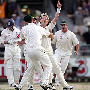 Andrew Strauss (left) trudges off as the Australian players congratulate Brett Lee