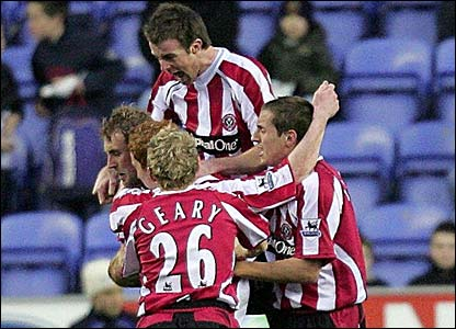 Rob Hulse is mobbed by his team-mates after scoring