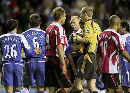 Referee Peter Walton is surrounded by players from both sides