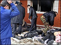 Сотрудники правоохранительных органов обследуют тела убитых боевиков