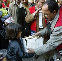 Red Crescent workers hand out food parcels to displaced Iraqis