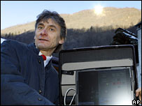 Viganella Mayor Pierfranco Midali holds the remote control computer as the giant mirror positioned on the hill behind