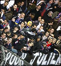 Paris Saint-Germain fans holding banner in memory of fan shot by police