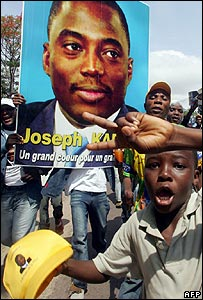 A boy celebrates next to banner depicting President Joseph Kabila