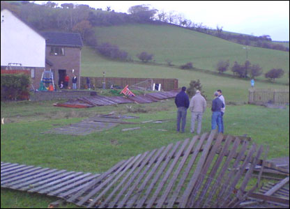 Villagers survey the damage which the tornado has left behind