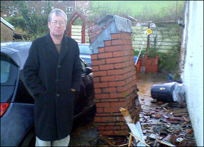 "Villager Kevin Walsh stands beside his fallen chimney stack. He said the tornado was an ""amazing, amazing experience"""