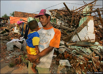 A man holds his son beside his destroyed home following the earthquake and tsunami in Bantul, Indonesia, on 1 June 2006