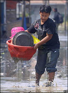 A resident evacuates belongings from her home flooded by mud in Porong, East Java, on 26 September 2006