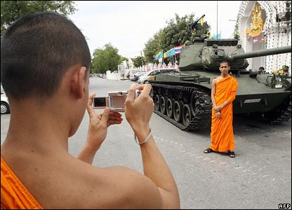 A Buddhist monk poses for pictures beside a tank in Bangkok on 21 September 2006