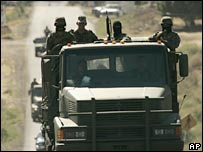 Mexican army soldiers patrol a road near the town of Aguililla, Mexico