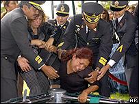 Familiares de los policías asesinados lloran durante el entierro