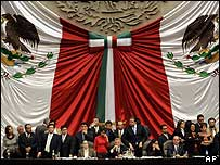 Mexican legislators stand around the podium of the Congress hall