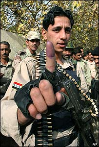Iraqi soldier shows his ink-stained finger after voting in December 2005 election