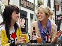 Two women smoke outside a pub in Glasgow