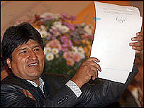 Evo Morales enseña la ley de reforma agraria firmada.
