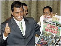 "Newly-elected Ecuador President Rafael Correa holds a newspaper reading ""The cod wins"""