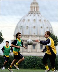 Young people play football in front of St Peter's Basilica at the Vatican