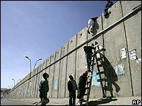 Palestinians climb West Bank barrier