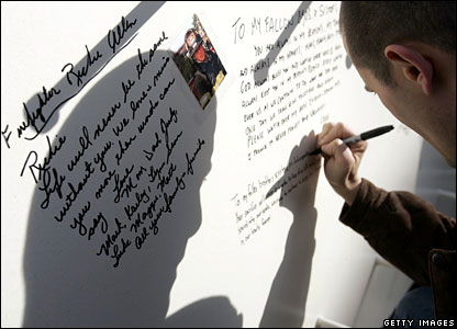A man writes a message on one of the columns for the Freedom Tower