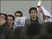 Iranian students burn the portraits of President Mahmoud Ahmadinejad