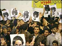 Iranian students hold President Ahmadinejad's pictures upside down