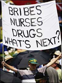 "A banner reads ""Bribes, nurses, drugs, what next?"""