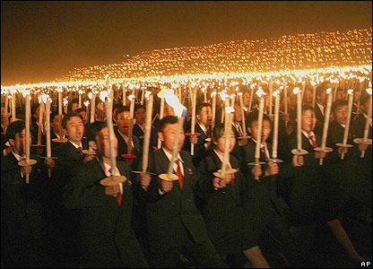 North Koreans carry torches for the 80th anniversary of the Down with Imperialism Union on 17 October 2006