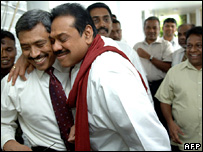 Sri Lankan Defence Ministry Secretary Gotabaya Rajapaksa (l) is hugged by elder brother Sri Lankan President Mahinda Rajapaksa (C) in Colombo, 01 December 2006 after the explosion