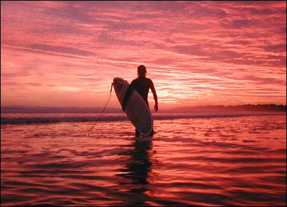 Surfer against pink sky