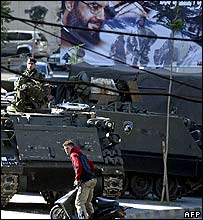 Lebanese soldier beneath poster of Hassan Nasrallah