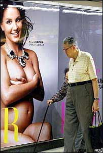 Pareja de ancianos japoneses pasan frente a un cartel publicitario