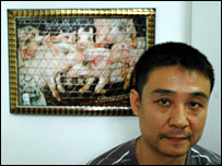Tran Luong with an image of pigs awaiting sale in a Vietnamese market