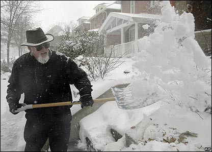 Robert Bigelow clears snow from the pavement in front of his home in Denver