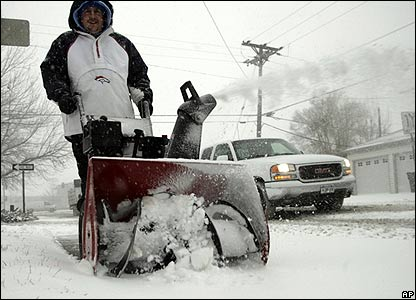 Thom Hartman uses a snow-blower to clear a pavement in Denver