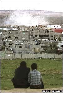 Palestinian boys look at smoke rising around Israeli bulldozers and tanks in Beit Hanoun