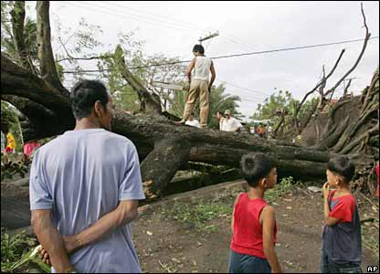 Workers clear a road off fallen trees in Candelaria, Quezon province