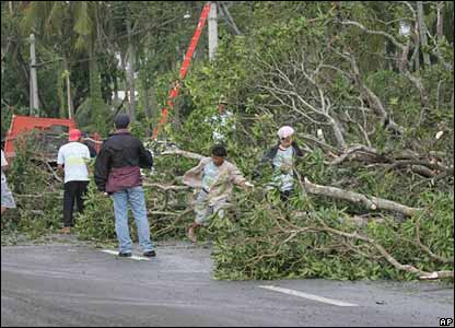 Rescuers clear a road in the Quezon province