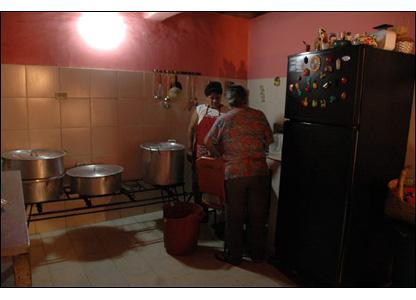 La comida del mercal tambi�n es enviada a varios hogares del barrio en donde se cocinan platos gratuitos para unas 150 personas y donde mujeres preparan el almuerzo y una merienda y los empacan en con