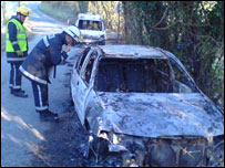 Firefighters examining the burnt out cars