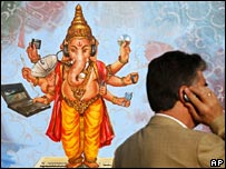 Man using mobile phone by poster showing Hindu god with modern technology equipment